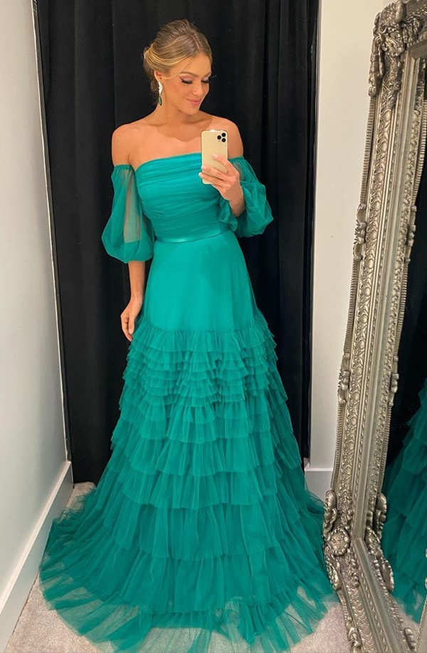 long green party dress with puffed sleeves and ruffles on the skirt